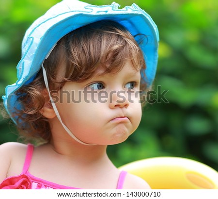 Angry baby girl looking in blue hat on summer background. Closeup portrait - stock photo
