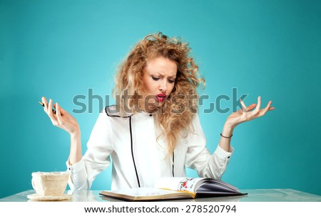 Angry beautiful blonde student reading a book, learning. Studio shot. - stock photo