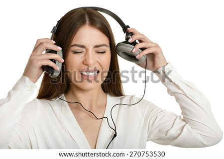 Angry beautiful girl and headphones on white background. - stock photo