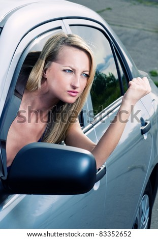 Angry blond young woman sitting in a car
