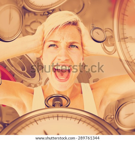 Angry blonde screaming and holding her head against grey vignette - stock photo
