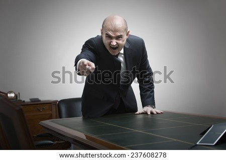 Angry boss behind of office table - stock photo