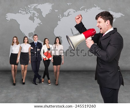 Angry boss. Businessman with megaphone standing in front of other busines people - stock photo