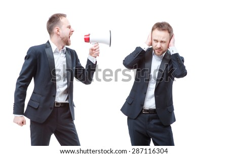 Angry boss. Concept of self-discipline. Bearded businessman shouting with megaphone shouting at him self, clone or twin, who covering ears with hands while standing isolated on white background. - stock photo