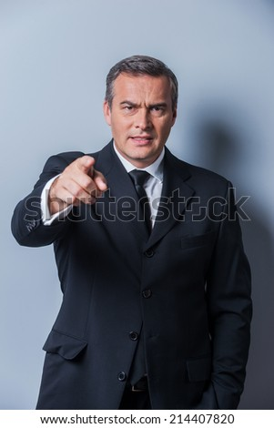 Angry boss. Furious mature man in formalwear pointing you while standing against grey background - stock photo