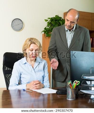 Angry boss scolding careless elderly female secretary for mistake at office - stock photo