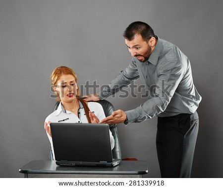 Angry boss shouting at his woman employee over a mistake she did on her laptop - stock photo