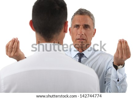 Angry boss talking to employee - stock photo