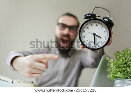 Angry boss with beard and glasses holds alarm clock screaming on camera - stock photo