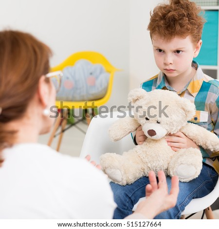 Angry boy during therapy session with psychologist
