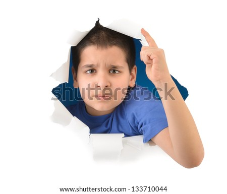 Angry boy looking through paper hole isolated on white background - stock photo