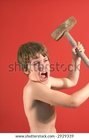 angry boy swinging slede hammer vertical - stock photo