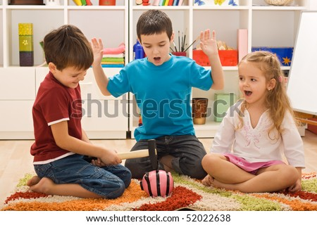 Angry boy try to break the pink piggy-bank and the other two children looking frightened