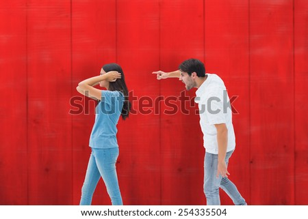 Angry boyfriend shouting at girlfriend against red wooden planks - stock photo