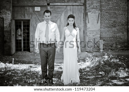 angry bride and groom standing and holding hands