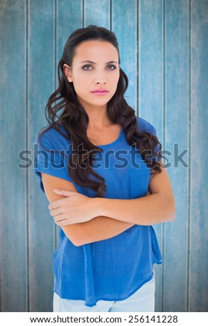 Angry brunette frowning at camera against wooden planks - stock photo
