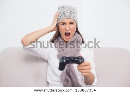 Angry brunette with winter hat on playing video games sitting on cosy sofa - stock photo
