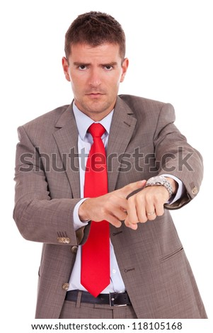 Angry business man pointing at his watch. Isolated on white.