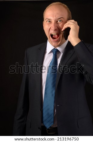 Angry business man screaming on cell mobile phone, portrait of young handsome businessman on black background, concept of executive yelling, conversation problem communication crisis  - stock photo