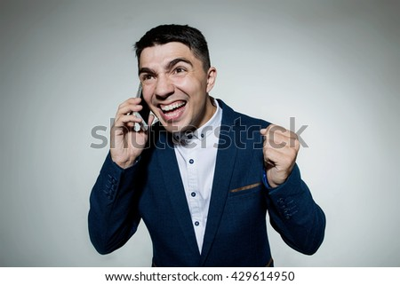 Angry business man talking on the phone isolated on a grey background.Human emotion, facial expression, feeling attitude. - stock photo