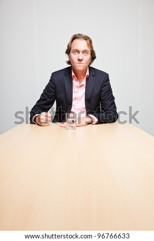 Angry business man with blond hair with glass of water sitting behind table in office isolated on white background