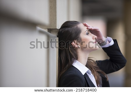 Angry business woman banging her head against a wall outside office building. - stock photo