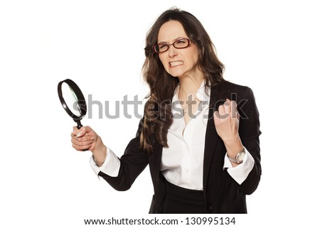 angry business woman is very upset with and a magnifying glass in hand - stock photo