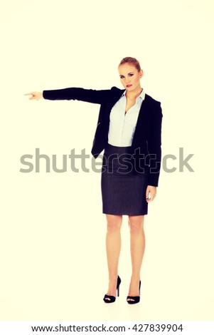 Angry business woman shows get out gesture - stock photo