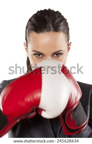 angry business woman with boxing gloves on a gray background