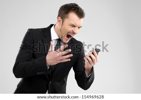 Angry businessman. Angry young man in formalwear shouting at mobile phone - stock photo