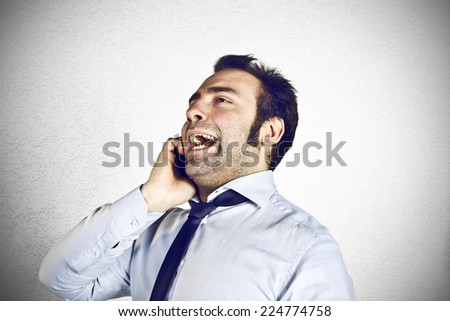 Angry businessman at the cell phone - stock photo