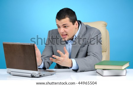 Angry businessman at work on blue background