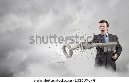 Angry businessman crashing stone key with punch - stock photo