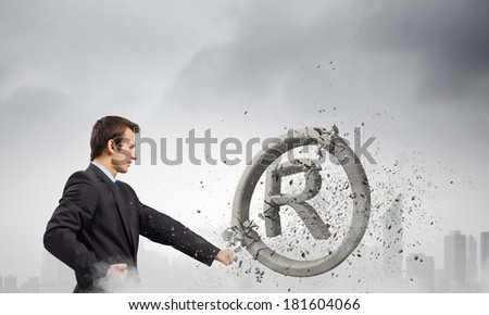 Angry businessman crashing stone trademark with karate punch