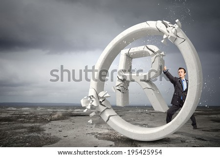 Angry businessman crashing stone trademark with karate punch - stock photo