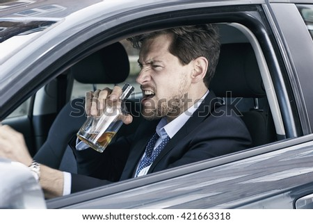 Angry businessman driving drunk - stock photo