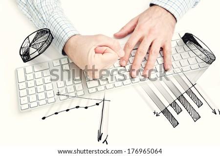 Angry businessman hitting computer keyboard, smashing infographic elements - stock photo