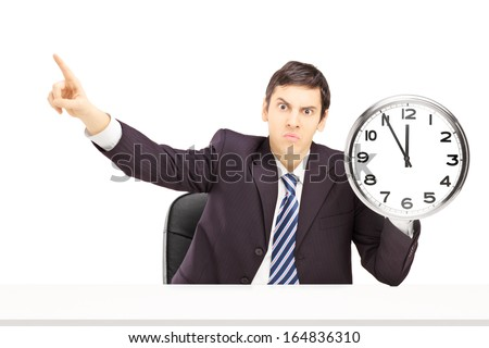 Angry businessman holding a clock and gesturing with his finger, isolated on white background - stock photo