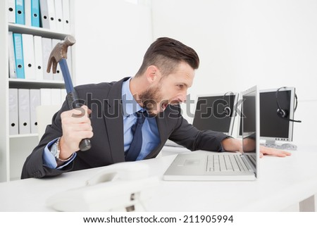 Angry businessman holding hammer over laptop in his office - stock photo