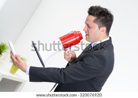 Angry businessman in an office, shouting on a megaphone, holding a mobile phone in the hand - stock photo