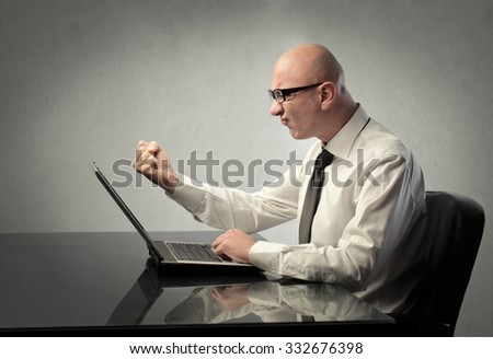 Angry businessman in front of a laptop