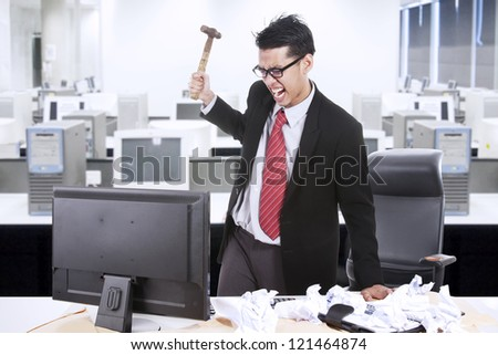 Angry businessman is about to throw a hammer at his computer in the office - stock photo