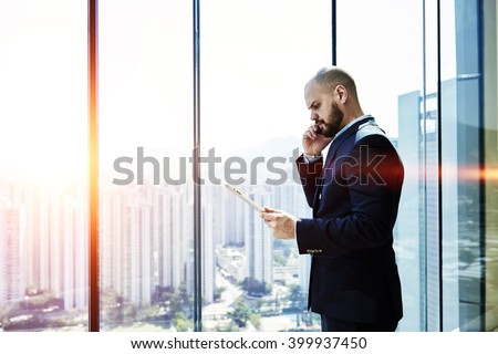 Angry businessman is calling via mobile phone to client, while is read on touch pad in e-mail about refusing to pay the for service company, while is standing near window with view of developed city - stock photo
