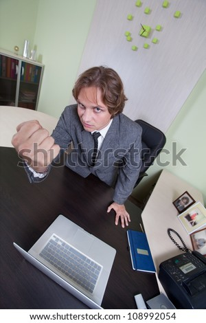 Angry businessman is shaking with his fist on the office background. - stock photo