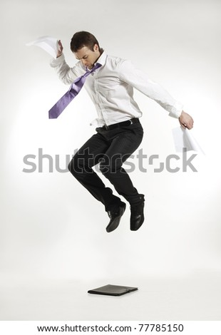 angry businessman jumping and stomping on a briefcase holding papers in his hands - stock photo