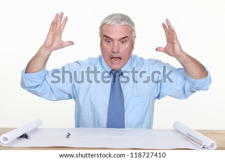 angry businessman looking at a blueprint - stock photo