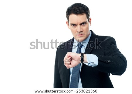 Angry businessman looking at his wristwatch - stock photo