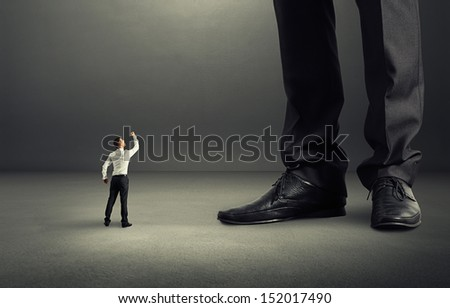 angry businessman looking up and showing fist to his big boss - stock photo