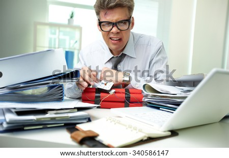 Angry businessman preparing dynamite at workplace