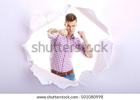 Angry Businessman punching into camera - Ripped torn paper